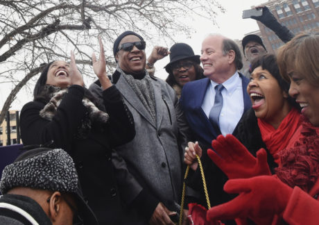 """Motown legend Stevie Wonder, center left, unveils the new street sign """"Stevie Wonder Avenue,"""" a portion of Milwaukee Street, along with Motown Museum chairwoman Robin Terry, far left, Detroit Mayor Mike Duggan, third right, City Council President Brenda Jones, second right, and Congresswoman Brenda Lawrence, far right, during a ceremony in Detroit on Wednesday, Dec. 21, 2016. (Daniel Mears/Detroit News via AP)"""